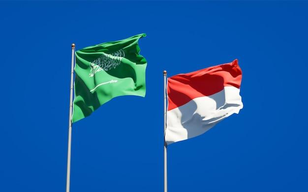 Belle bandiere di stato nazionali dell'arabia saudita e dell'indonesia insieme sul cielo blu