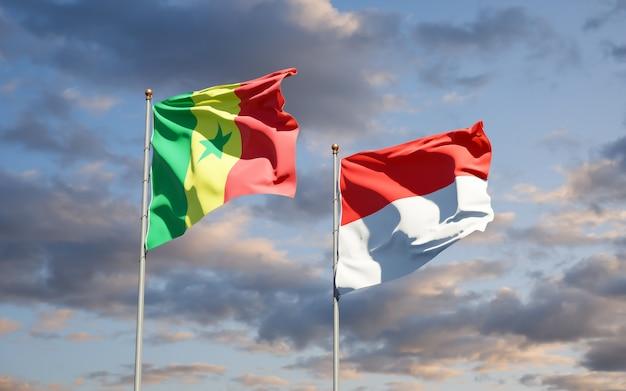 Belle bandiere di stato nazionali del senegal e dell'indonesia insieme sul cielo blu