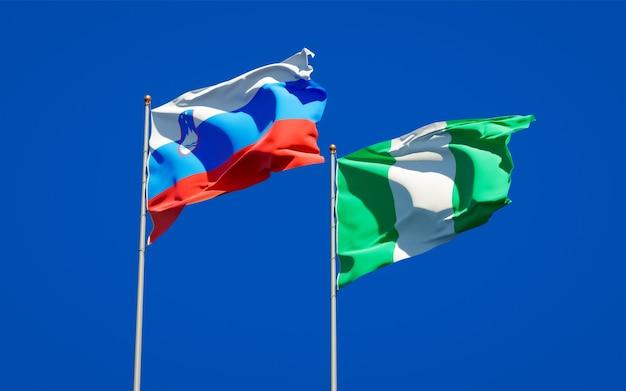 Belle bandiere di stato nazionali della slovenia e della nigeria insieme sul cielo blu