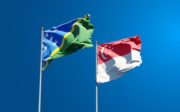 Belle bandiere di stato nazionali delle isole salomone e singapore insieme