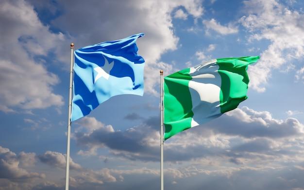 Belle bandiere di stato nazionali della somalia e della nigeria insieme sul cielo blu