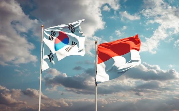Belle bandiere di stato nazionali della corea del sud e indonesia insieme sul cielo blu
