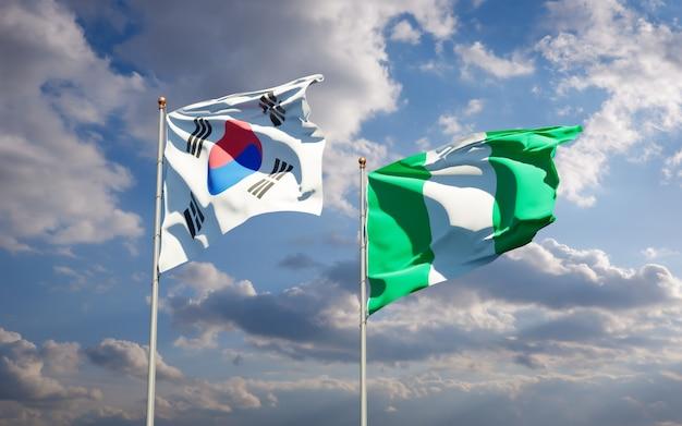 Belle bandiere di stato nazionali della corea del sud e della nigeria insieme sul cielo blu