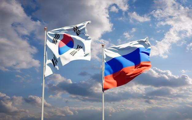 Belle bandiere di stato nazionali della corea del sud e della russia insieme sul cielo blu. grafica 3d