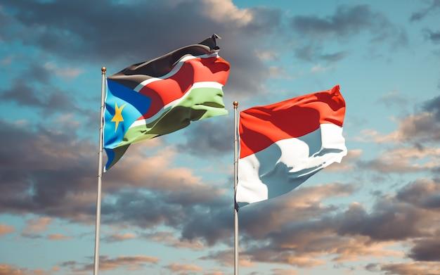 Belle bandiere di stato nazionali del sud sudan e indonesia insieme sul cielo blu