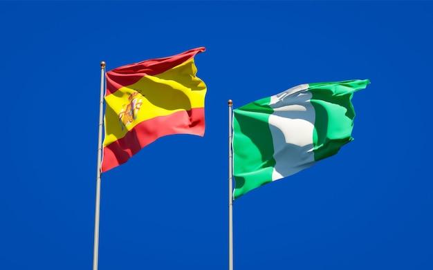 Belle bandiere di stato nazionali di spagna e nigeria insieme sul cielo blu