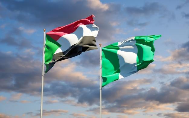 Belle bandiere di stato nazionali del sudan e della nigeria insieme sul cielo blu