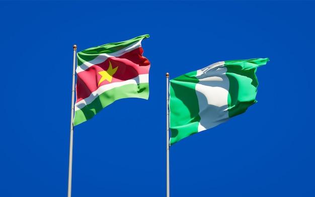 Belle bandiere dello stato nazionale del suriname e della nigeria insieme sul cielo blu