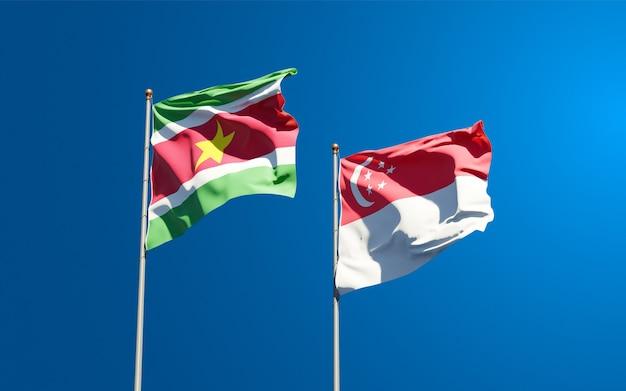 Belle bandiere nazionali dello stato del suriname e singapore insieme