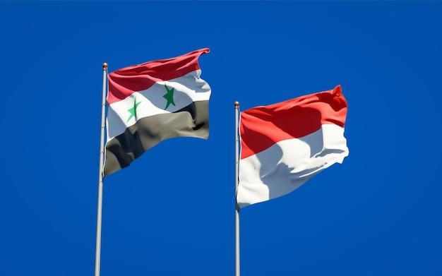 Belle bandiere dello stato nazionale della siria e dell'indonesia insieme sul cielo blu