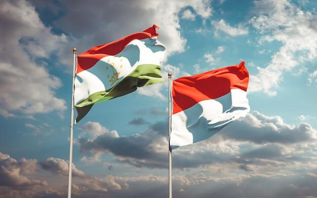 Belle bandiere di stato nazionali del tagikistan e dell'indonesia insieme sul cielo blu