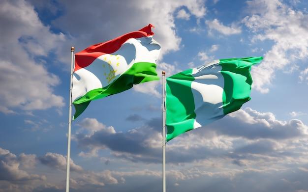 Belle bandiere di stato nazionali del tagikistan e della nigeria insieme sul cielo blu