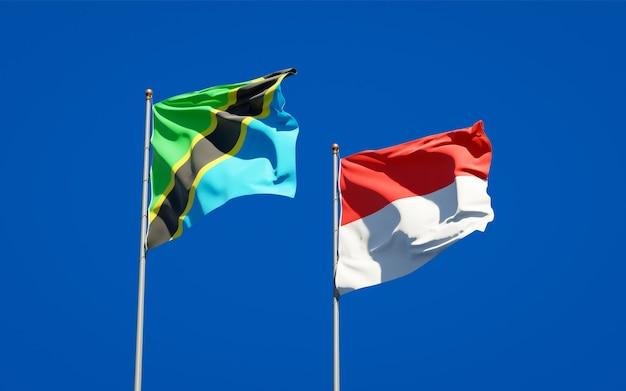 Belle bandiere dello stato nazionale della tanzania e dell'indonesia insieme sul cielo blu