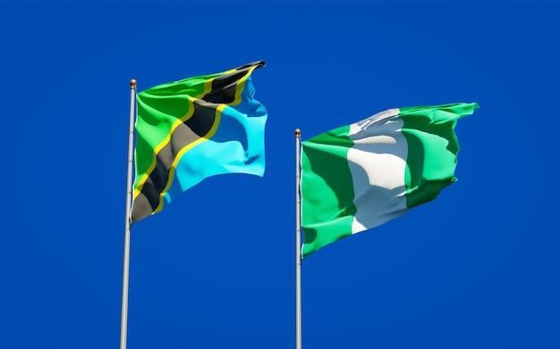 Belle bandiere di stato nazionali della tanzania e della nigeria insieme sul cielo blu