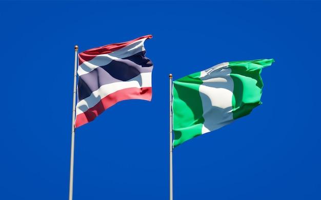 Belle bandiere di stato nazionali della thailandia e della nigeria insieme sul cielo blu
