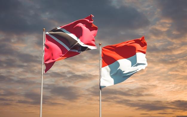 Belle bandiere dello stato nazionale di trinidad e tobago e indonesia insieme sul cielo blu