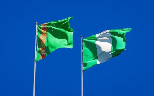 Belle bandiere dello stato nazionale del turkmenistan e della nigeria insieme sul cielo blu