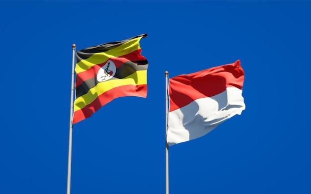 Belle bandiere di stato nazionali dell'uganda e dell'indonesia insieme sul cielo blu