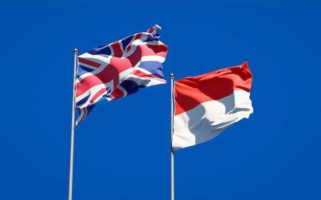 Belle bandiere dello stato nazionale del regno unito e dell'indonesia insieme sul cielo blu
