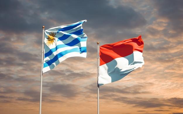 Belle bandiere di stato nazionali dell'uruguay e dell'indonesia insieme sul cielo blu