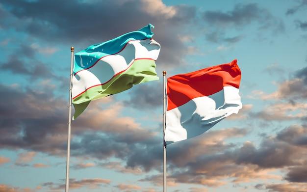 Belle bandiere di stato nazionali dell'uzbekistan e dell'indonesia insieme sul cielo blu