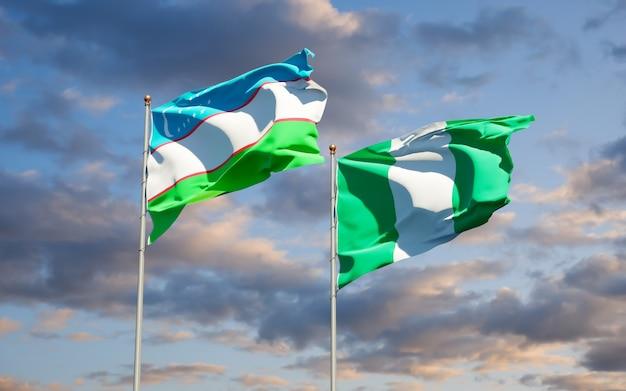 Belle bandiere dello stato nazionale dell'uzbekistan e della nigeria insieme sul cielo blu