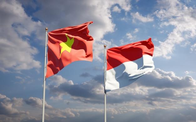 Belle bandiere di stato nazionali del vietnam e dell'indonesia insieme sul cielo blu