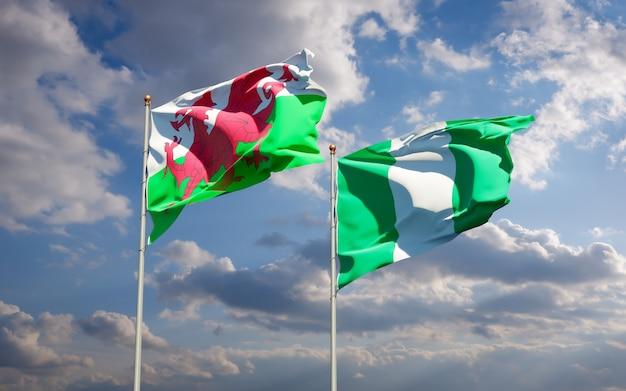 Belle bandiere di stato nazionali del galles e della nigeria insieme sul cielo blu