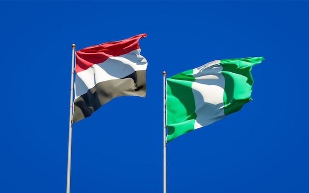 Belle bandiere di stato nazionali dello yemen e della nigeria insieme sul cielo blu