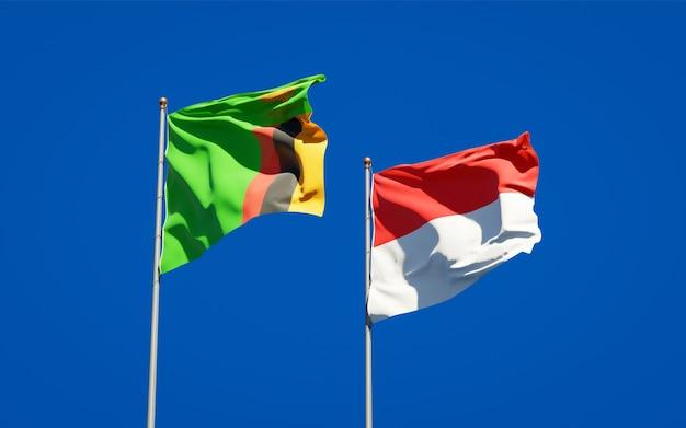 Belle bandiere di stato nazionali dello zambia e dell'indonesia insieme sul cielo blu