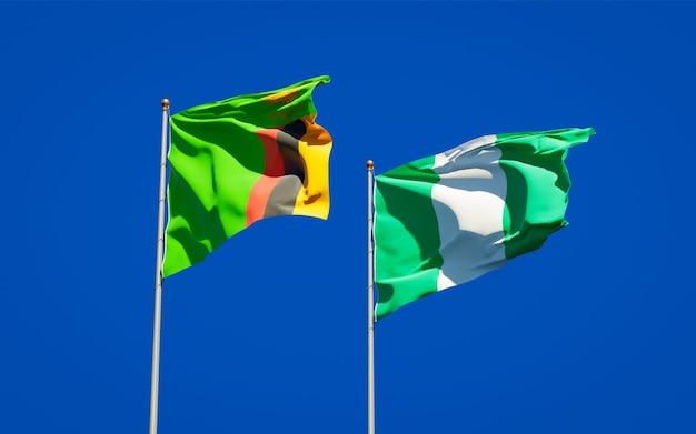 Belle bandiere di stato nazionali dello zambia e della nigeria insieme sul cielo blu