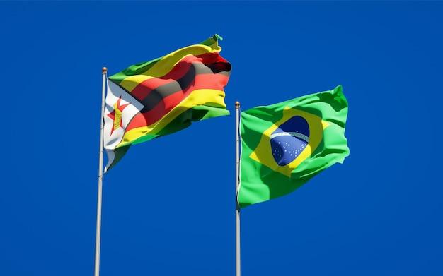 Belle bandiere dello stato nazionale dello zimbabwe e del brasile insieme sul cielo blu