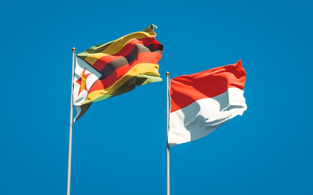 Belle bandiere di stato nazionali dello zimbabwe e dell'indonesia insieme sul cielo blu