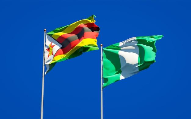 Belle bandiere di stato nazionali dello zimbabwe e della nigeria insieme sul cielo blu