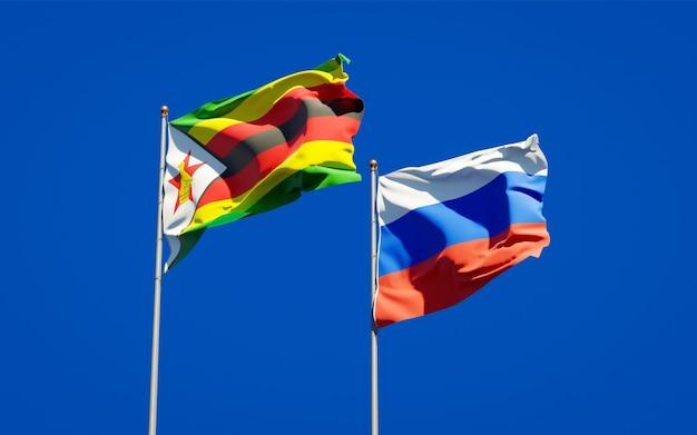 Belle bandiere di stato nazionali dello zimbabwe e della russia insieme sul cielo blu. grafica 3d