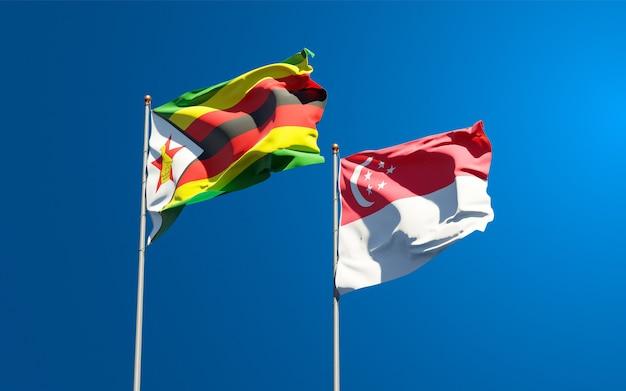 Belle bandiere di stato nazionali dello zimbabwe e singapore insieme