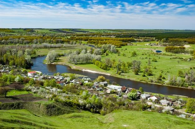 Bellissimo paesaggio naturale di un villaggio costruito intorno a un fiume in una calda giornata di sole autunnale contro un cielo blu. concetto di vita di campagna. copyspace