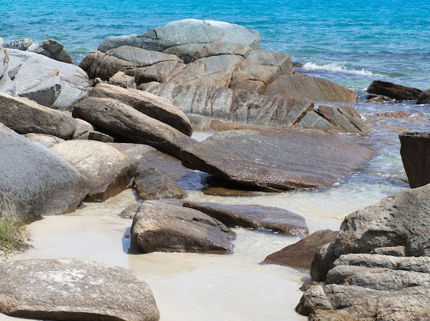 Belle rocce naturali sulla spiaggia sabbiosa e onde del mare turchese.