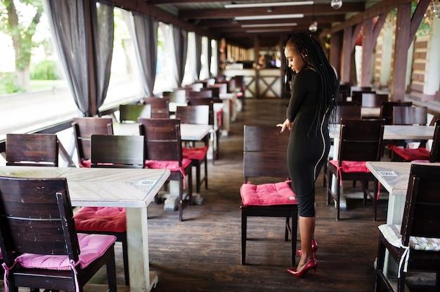 La bella giovane donna africana naturale con i capelli afro indossa un abito nero, posata al caffè con terrazza estiva.