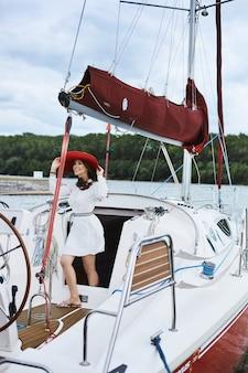 Bella ragazza bruna modello alla moda in breve bianco elegante abito sorridente, regolando il suo cappello rosso alla moda e in posa su una nave yacht al mare