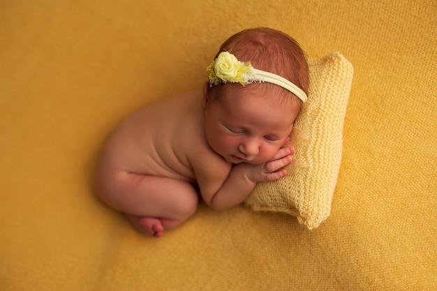 Bello neonato che dorme su un colore giallo
