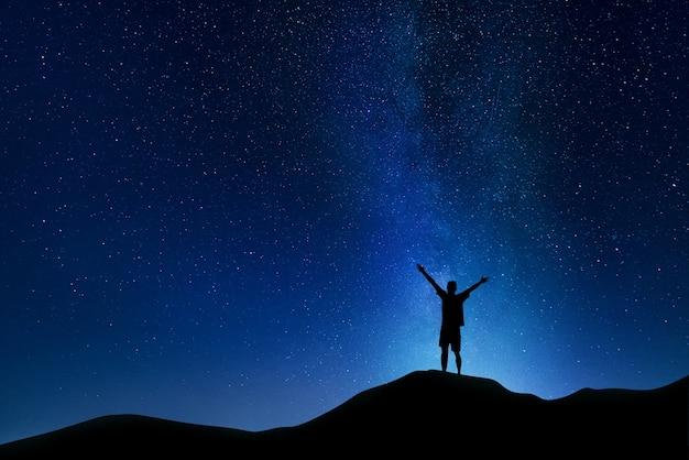 Bellissimo paesaggio notturno della via lattea nel cielo nuvoloso e silhouette di un giovane ragazzo con le mani in alto.