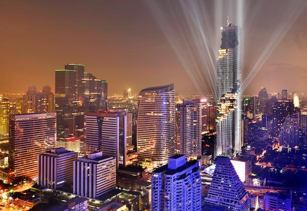 Bella vista di paesaggio urbano della luce notturna della costruzione moderna di affari dell'ufficio a bangkok, tailandia.