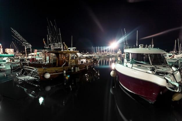 Bellissimo scatto notturno di barche in legno e a motore ormeggiate al porto di mare
