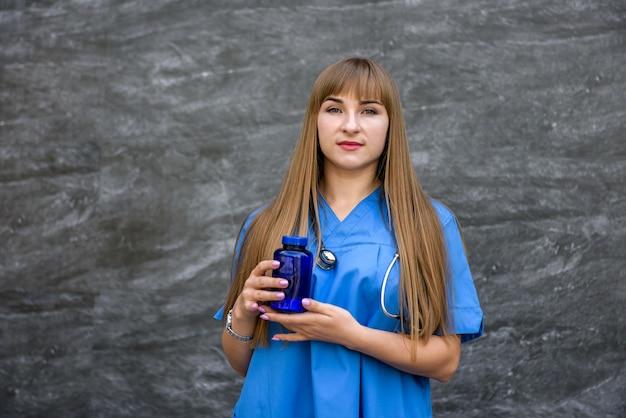 Bella infermiera in uniforme blu su sfondo grigio. concetto medico.