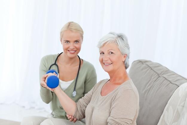 Bella infermiera che aiuta il suo paziente a fare esercizi