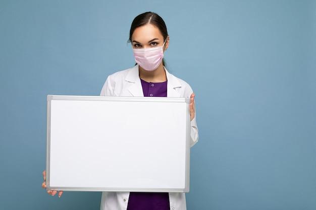 Bella infermiera in maschera protettiva e camice medico bianco che tiene una lavagna magnetica bianca vuota