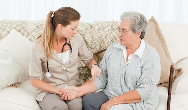 Bella infermiera prendendo il polso del suo paziente a casa