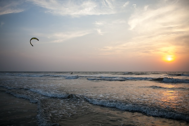 Bellissimo kitesurfer al tramonto sull'oceano sulle onde arambol goa india