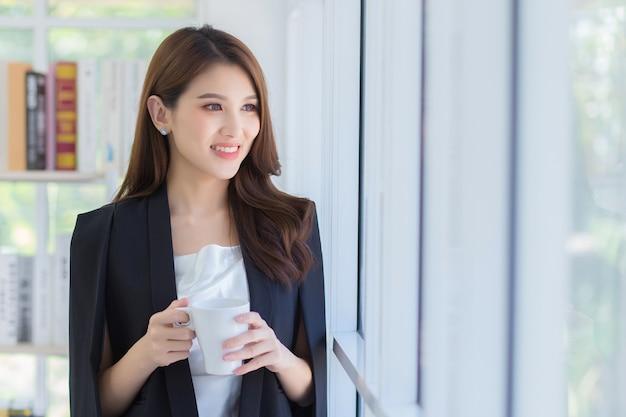 Una bella signora dell'ufficio che sorride e guarda fuori dalla finestra mentre tiene in mano una tazza di caffè